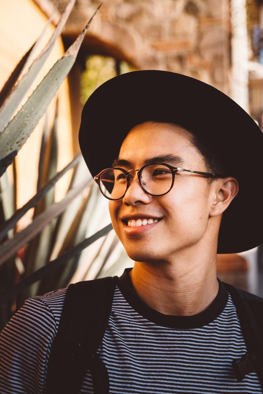smiling man wearing black framed eyeglasses and hat