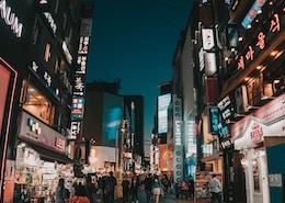 people walking between tall buildings