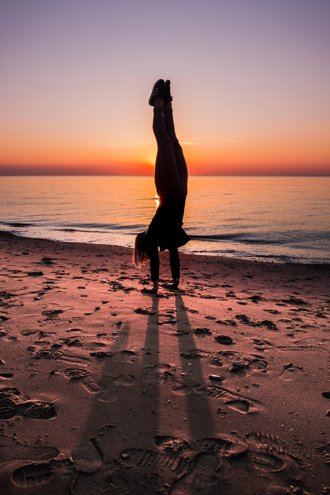 Handstand on the beach in Denmark during sunset.