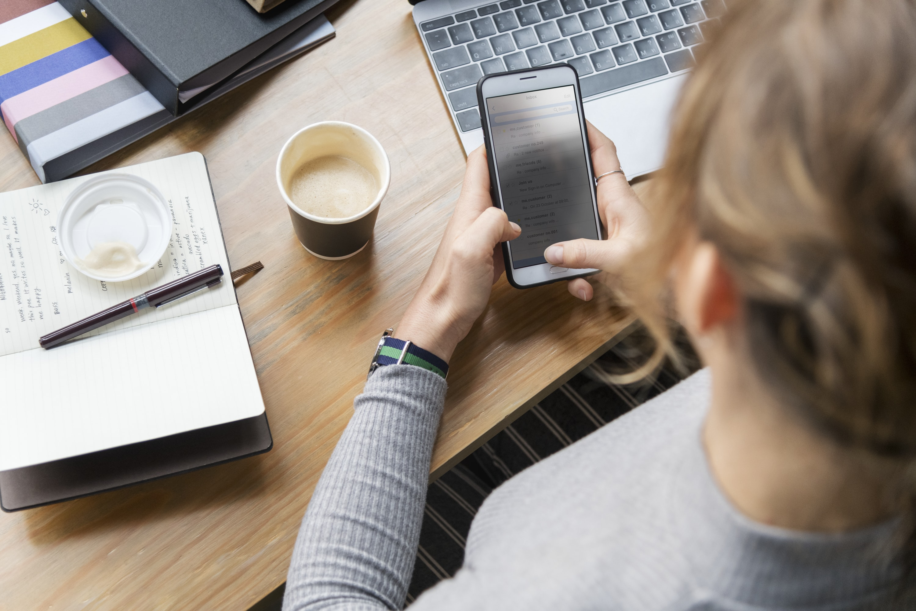 woman operating smartphone in front of laptop and cup of coffee