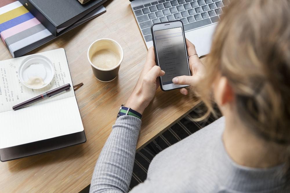 woman operating smartphone in front of laptop and cup of coffee, sifat boros, hindari boros, sifat menghambur-hamburkan uang