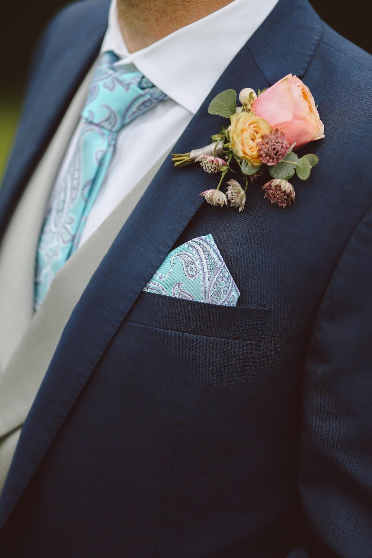 man in black formal coat and teal necktie