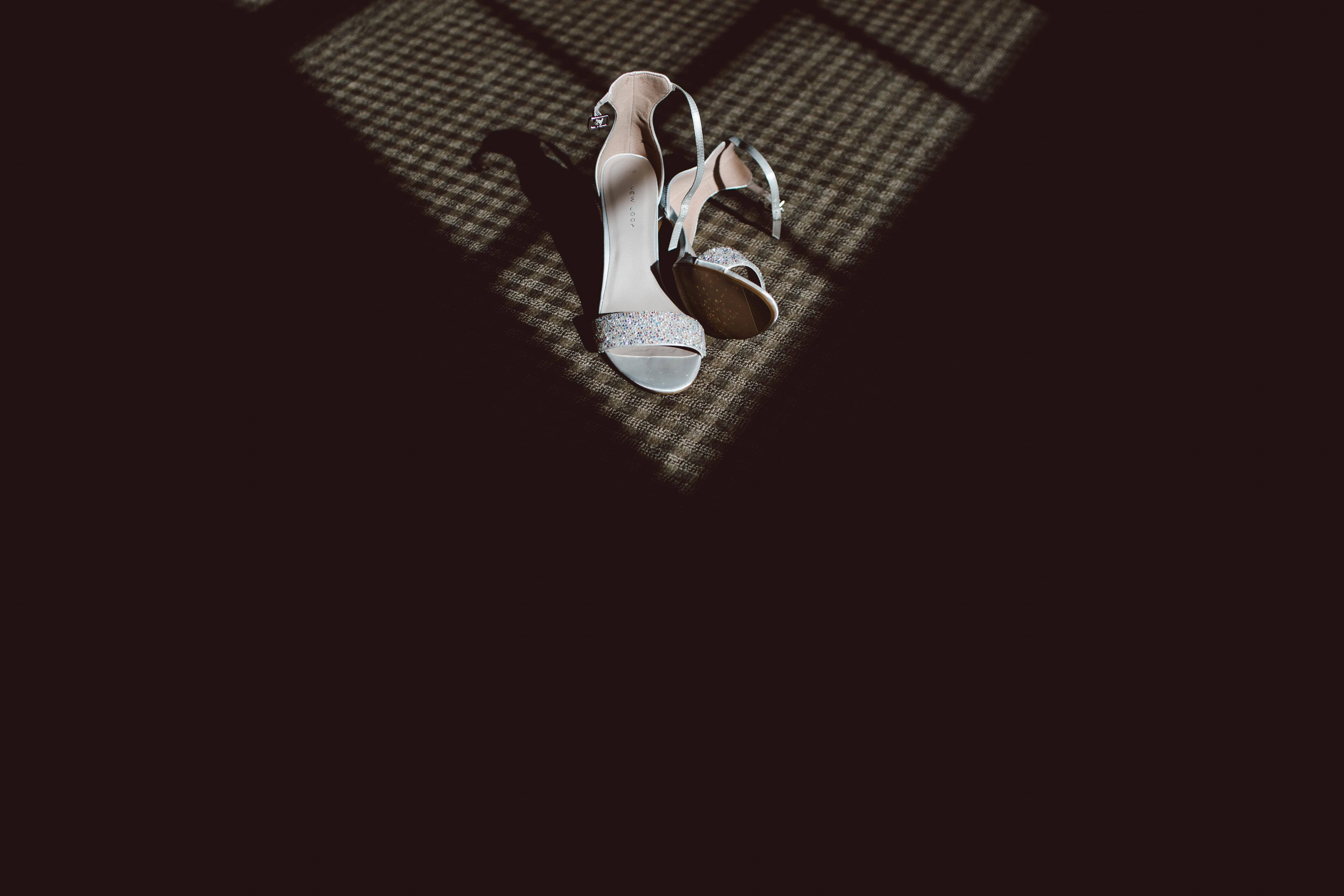 pair of white heels against black shadow