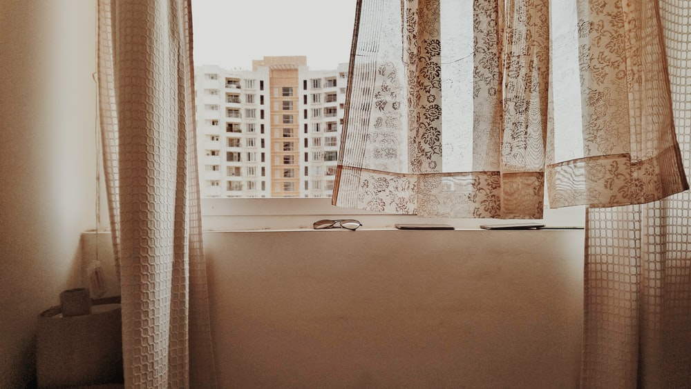 white and brown building see through window during daytime