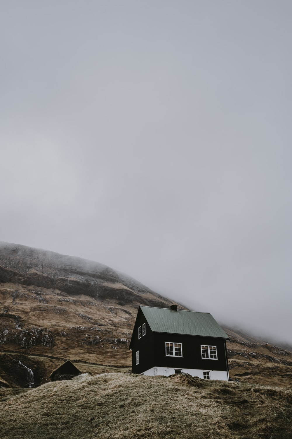 black and white wooden house on top of hill