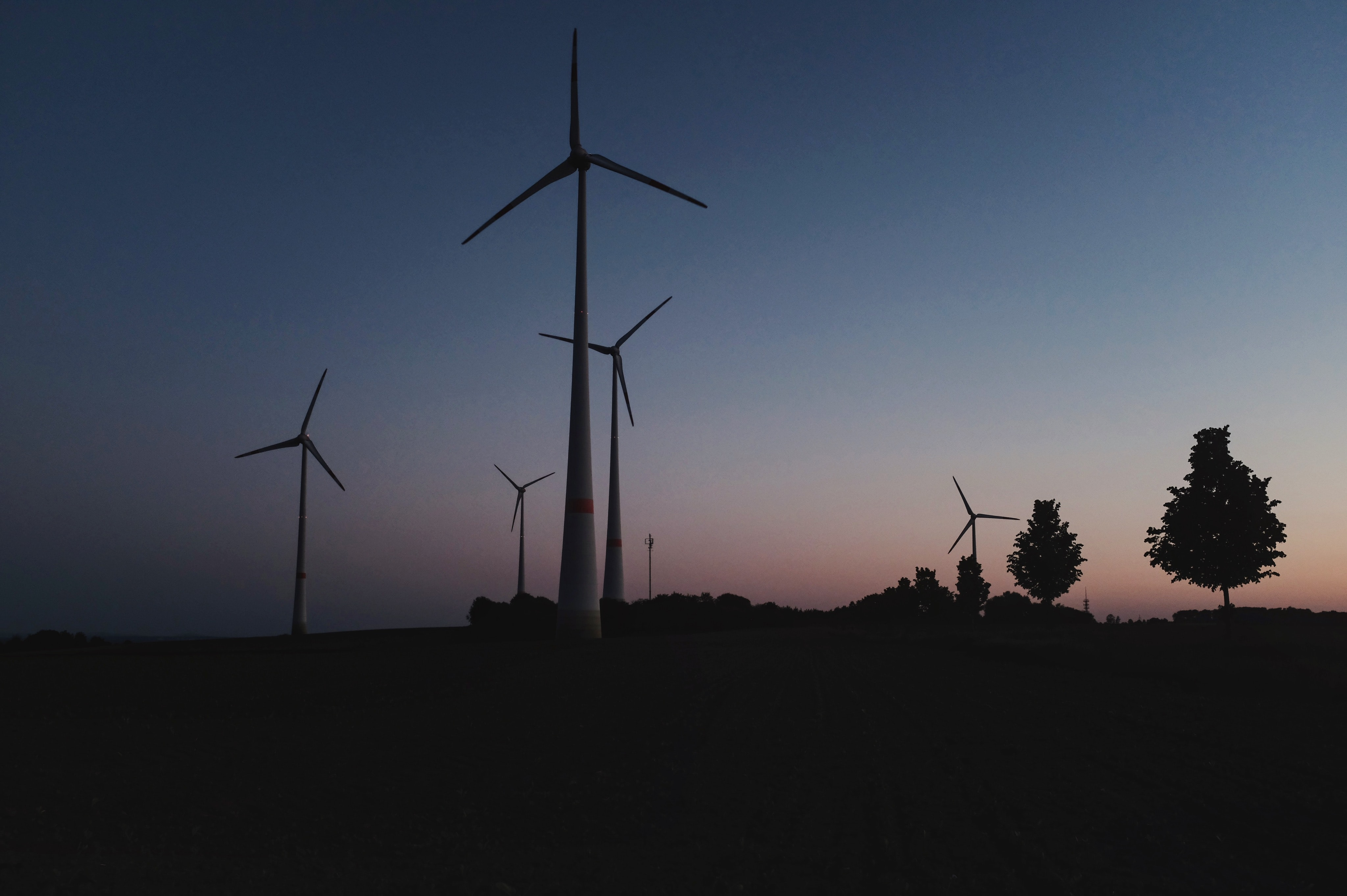 wind turbines silhouette under blue and white sky