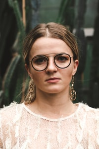 woman wearing eyeglasses and white lace top