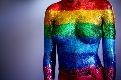 An 18 year old person covered in rainbow body glitter in support of the LGBTQ community and to celebrate gay pride 2018. We used a synthetic cosmetics brush to paint clear hair gel on their torso and then they laid down and I sprinkled the glitter on their body, one stripe at a time. We were able to touch up by dabbing more glitter on after they stood up. We used water-proof adhesive bandages to cover the sensitive areas on the chest and the belly-button.