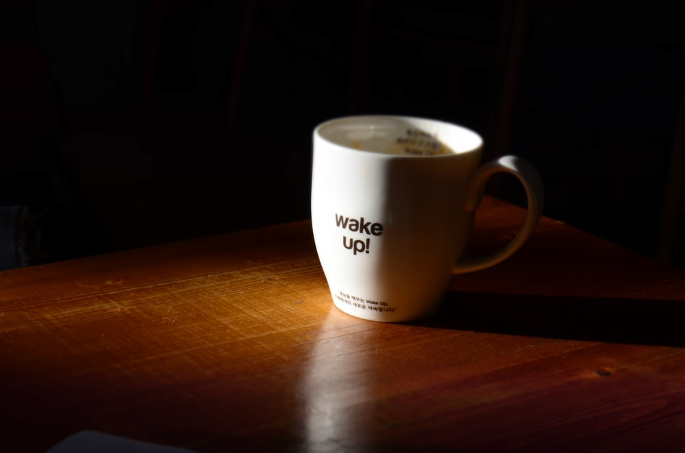 closeup photo of white cup on wooden surface
