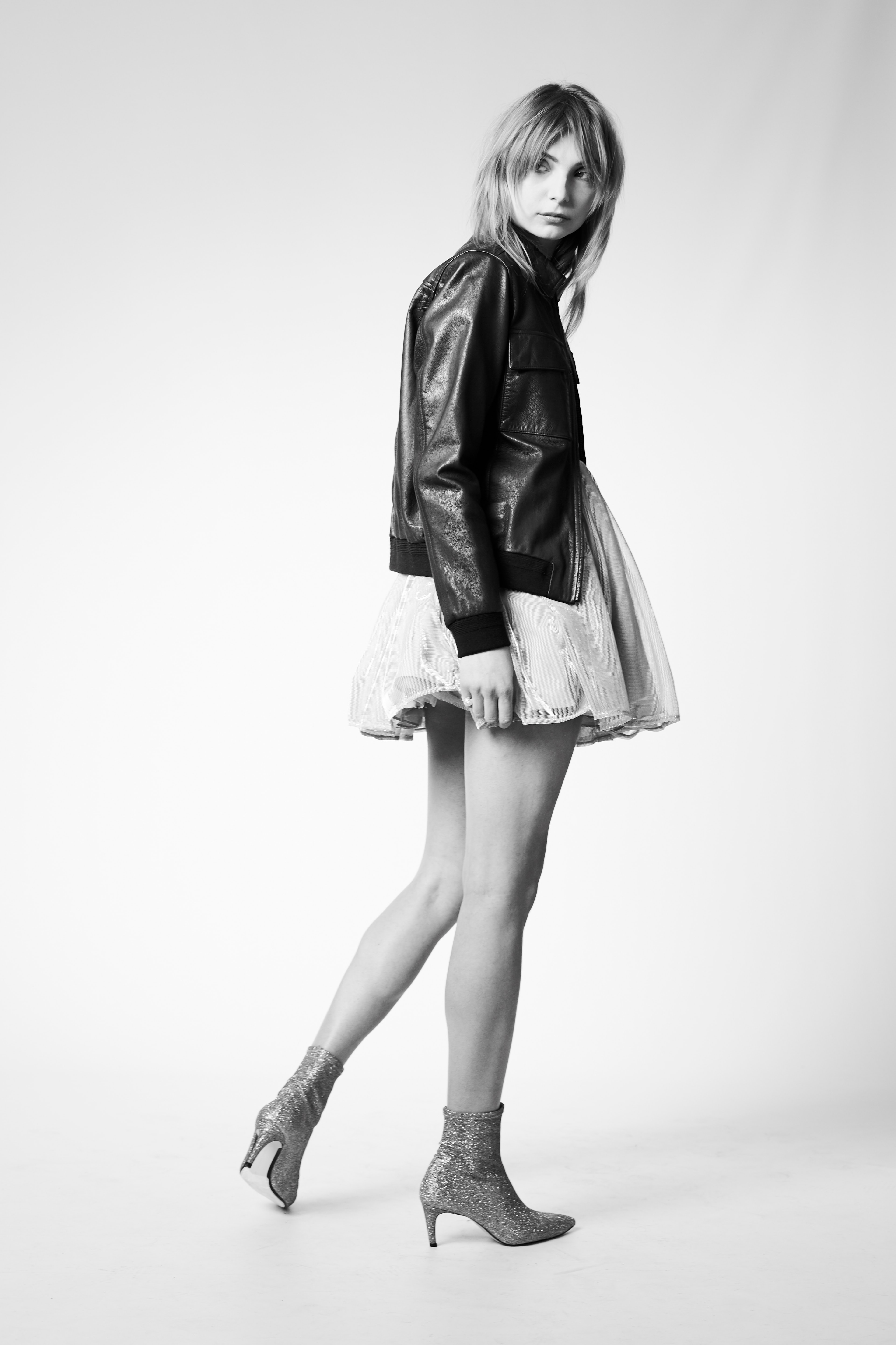 greyscale photo of woman in jacket, skirt, and heeled booties