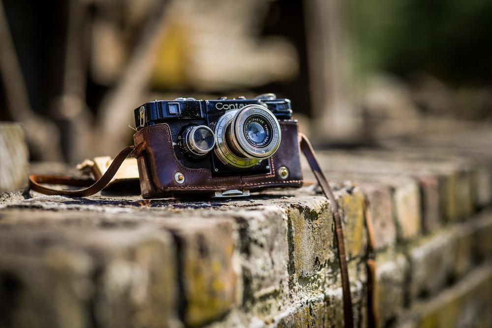black SLR camera on brown brick surface