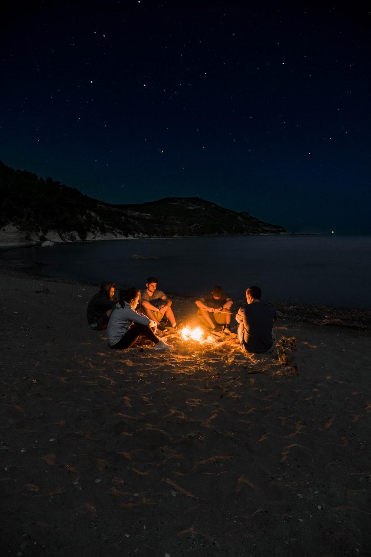 people sitting near campfire near seashore