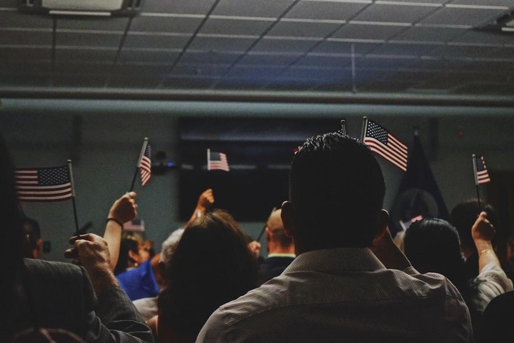 people holding flag of U.S.A miniature