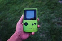person holding a green Gameboy color console