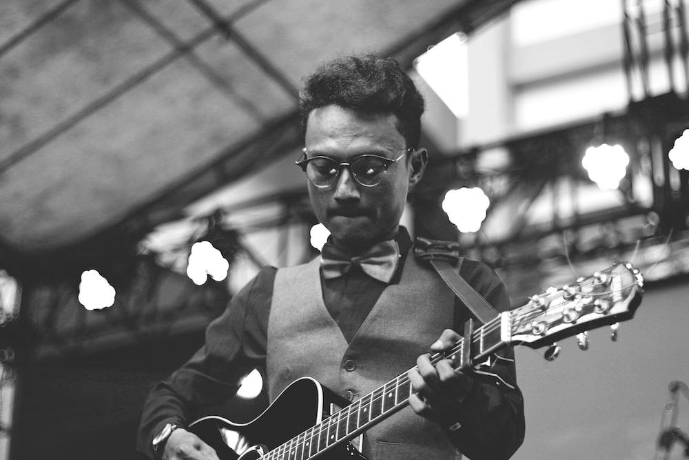 greyscale photo of man playing guitar