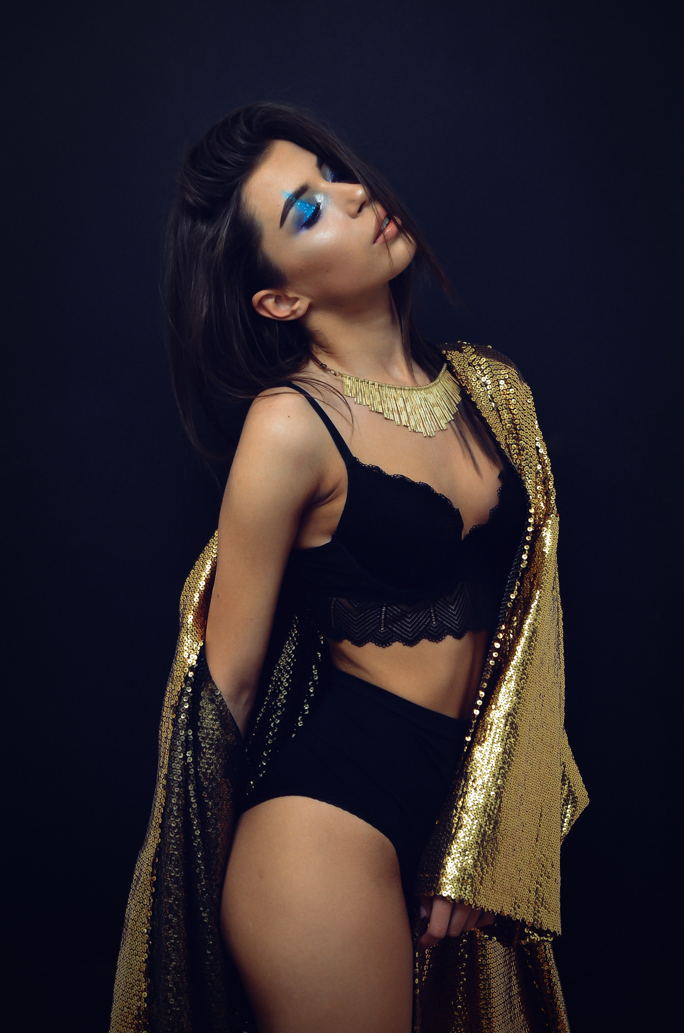 woman wearing black bra and panty with gold scarf
