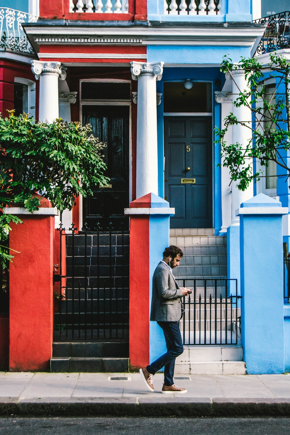 man using smartphone passing by blue and red houses