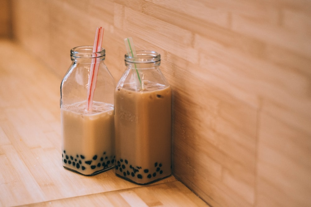 two clear glass jars with straws
