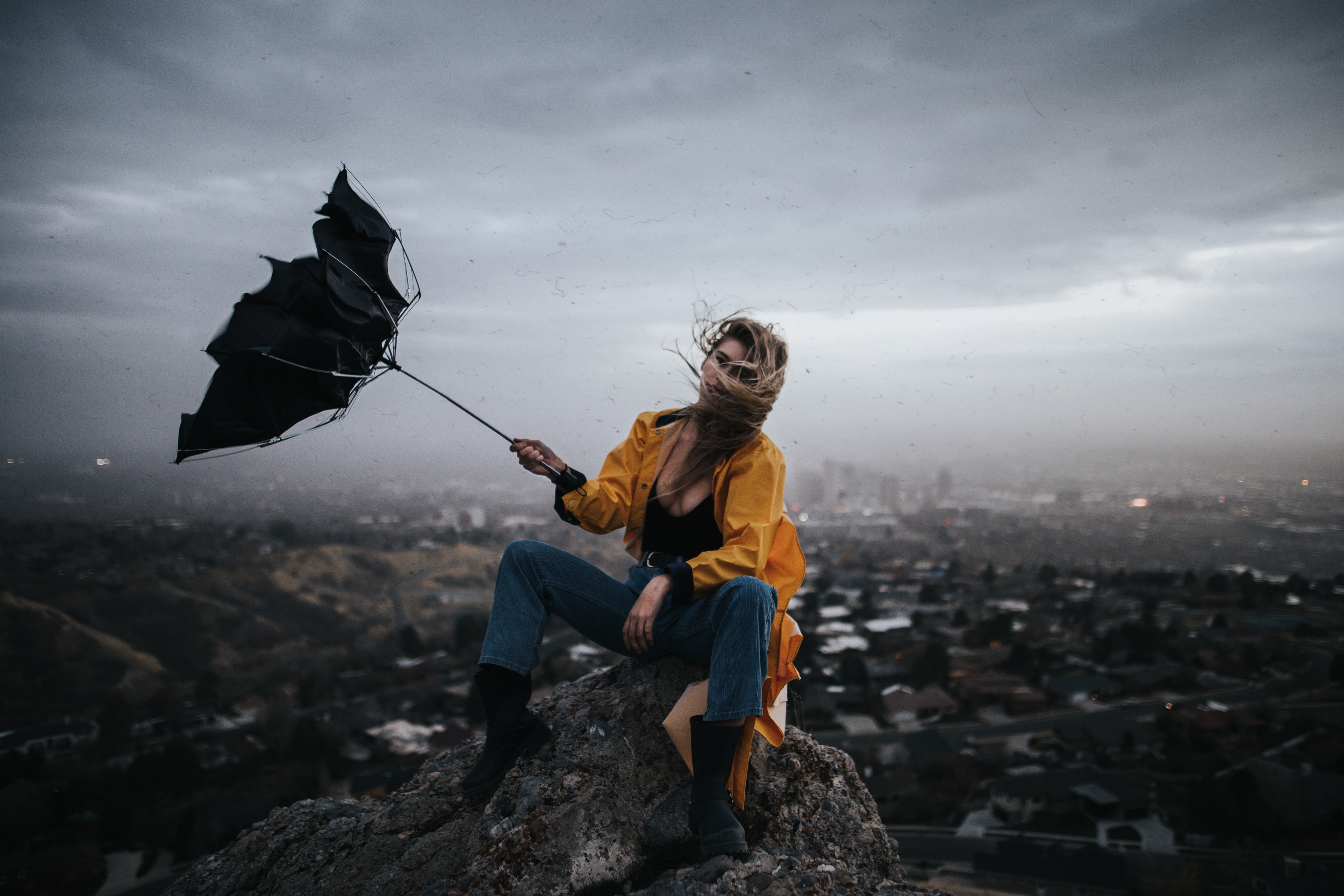 woman sitting on elevated rocky ground holding nearly flown umbrella overlooking city