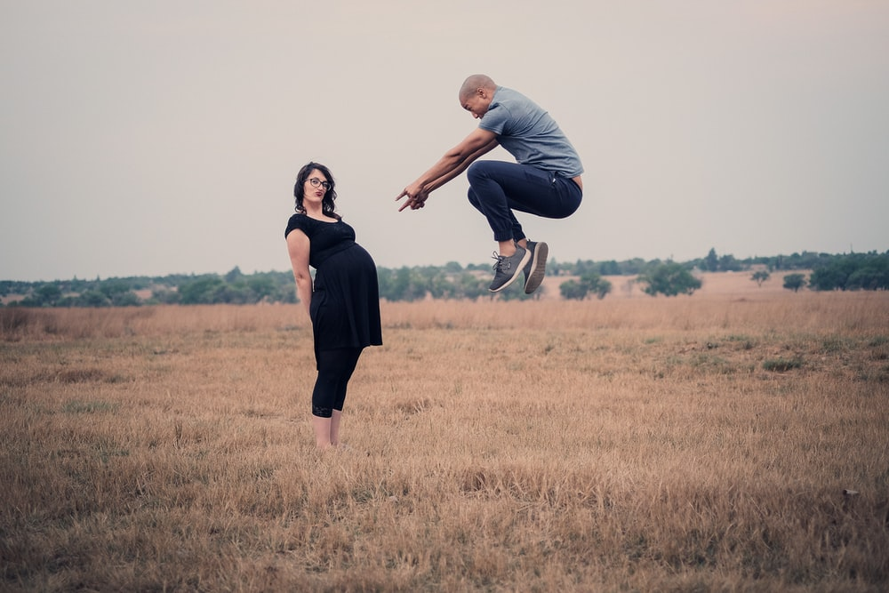 man jumping in front of woman standing on field