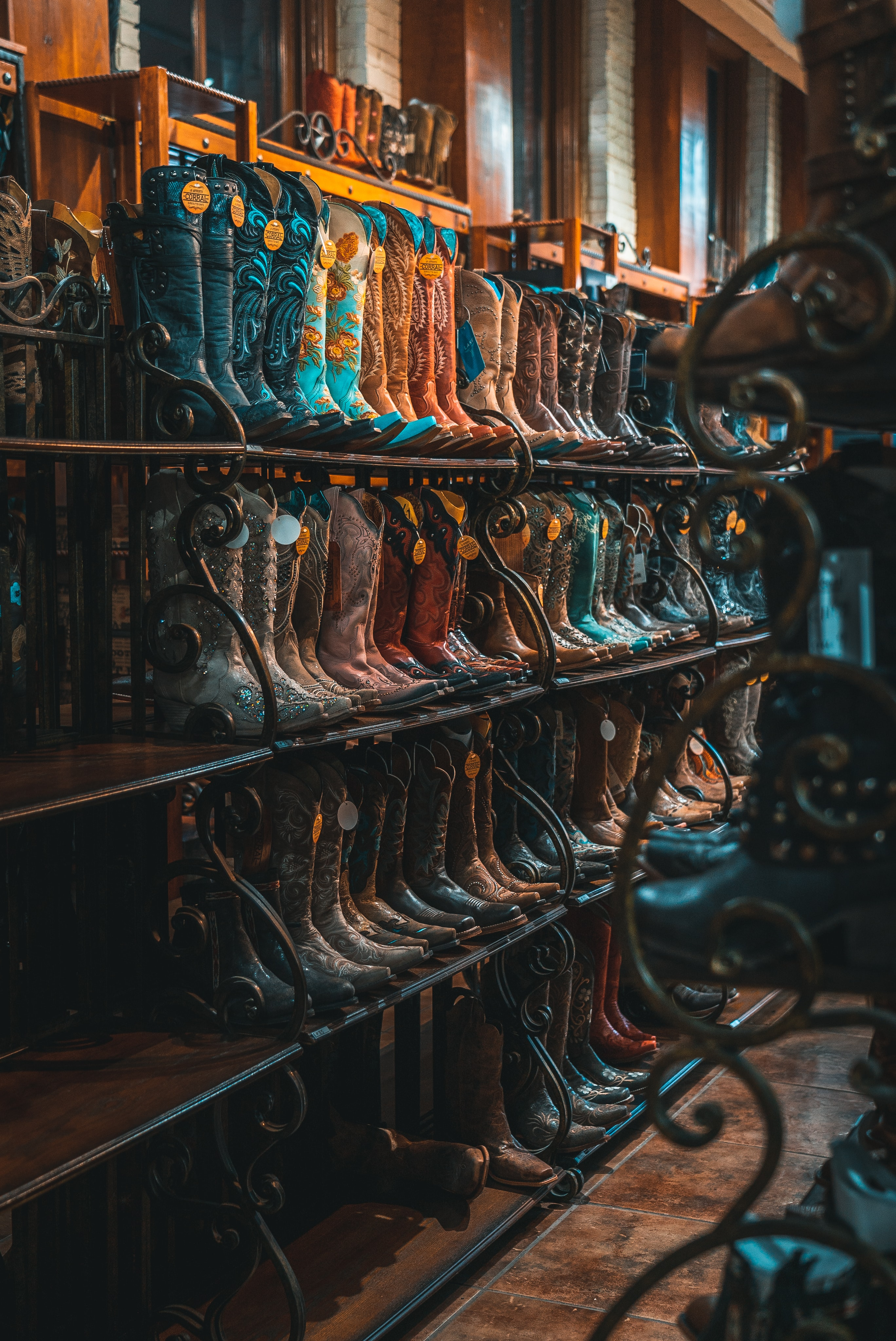 brown and blue leather cowboy boots on rack