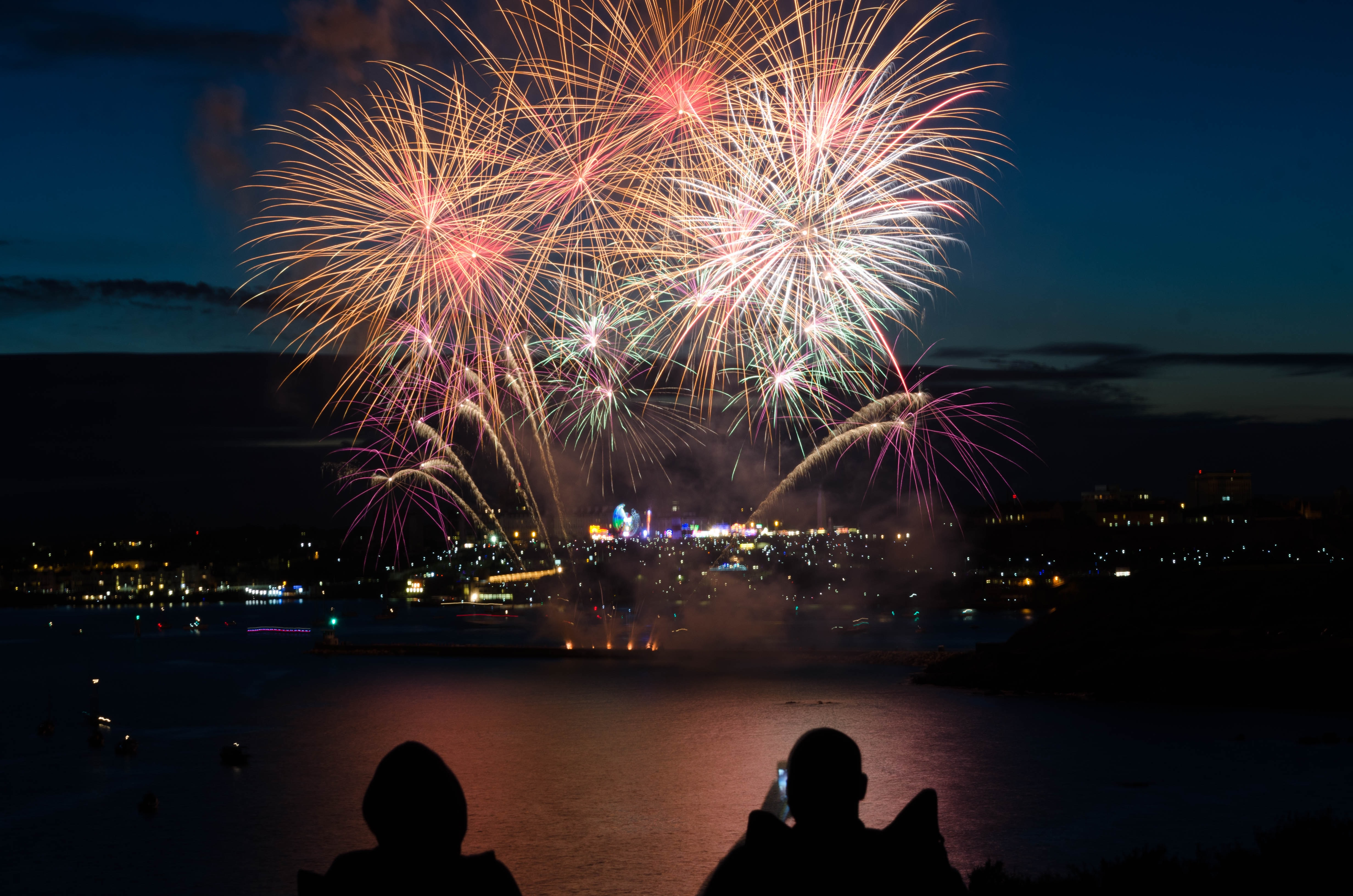silhouette of two person taking photo of fireworks