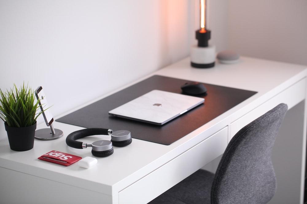 gray laptop on desk beside headphones