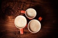 three red ceramic mugs with gray liquid inside