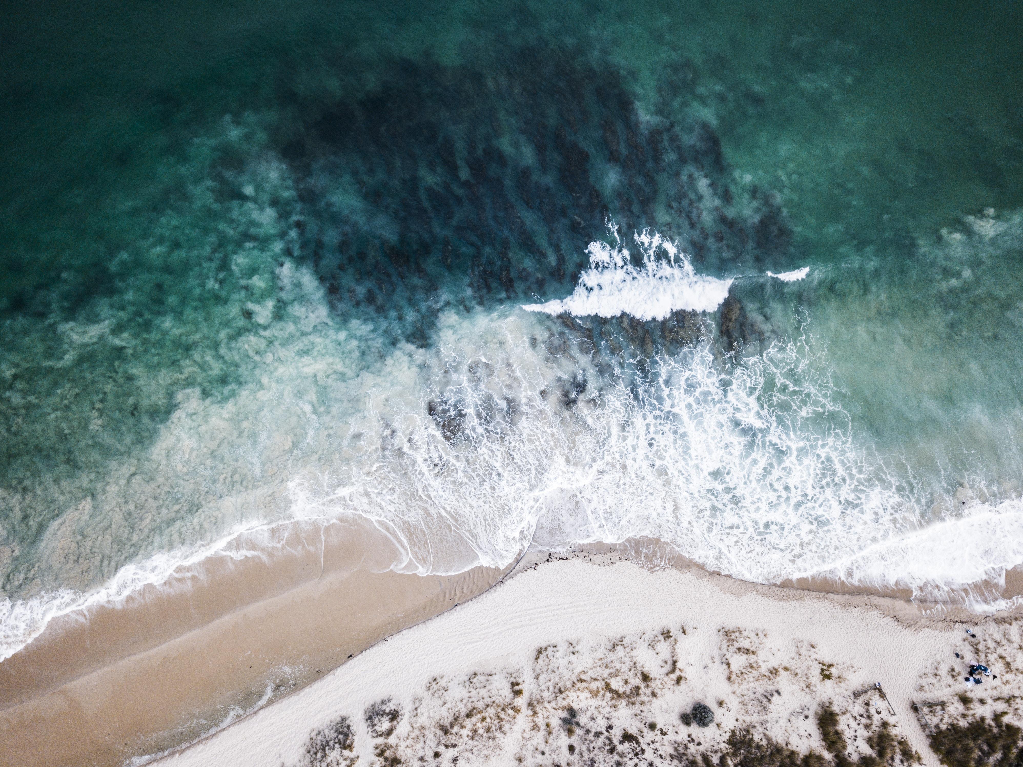 high-angle photo of ocean waves crashing on shore
