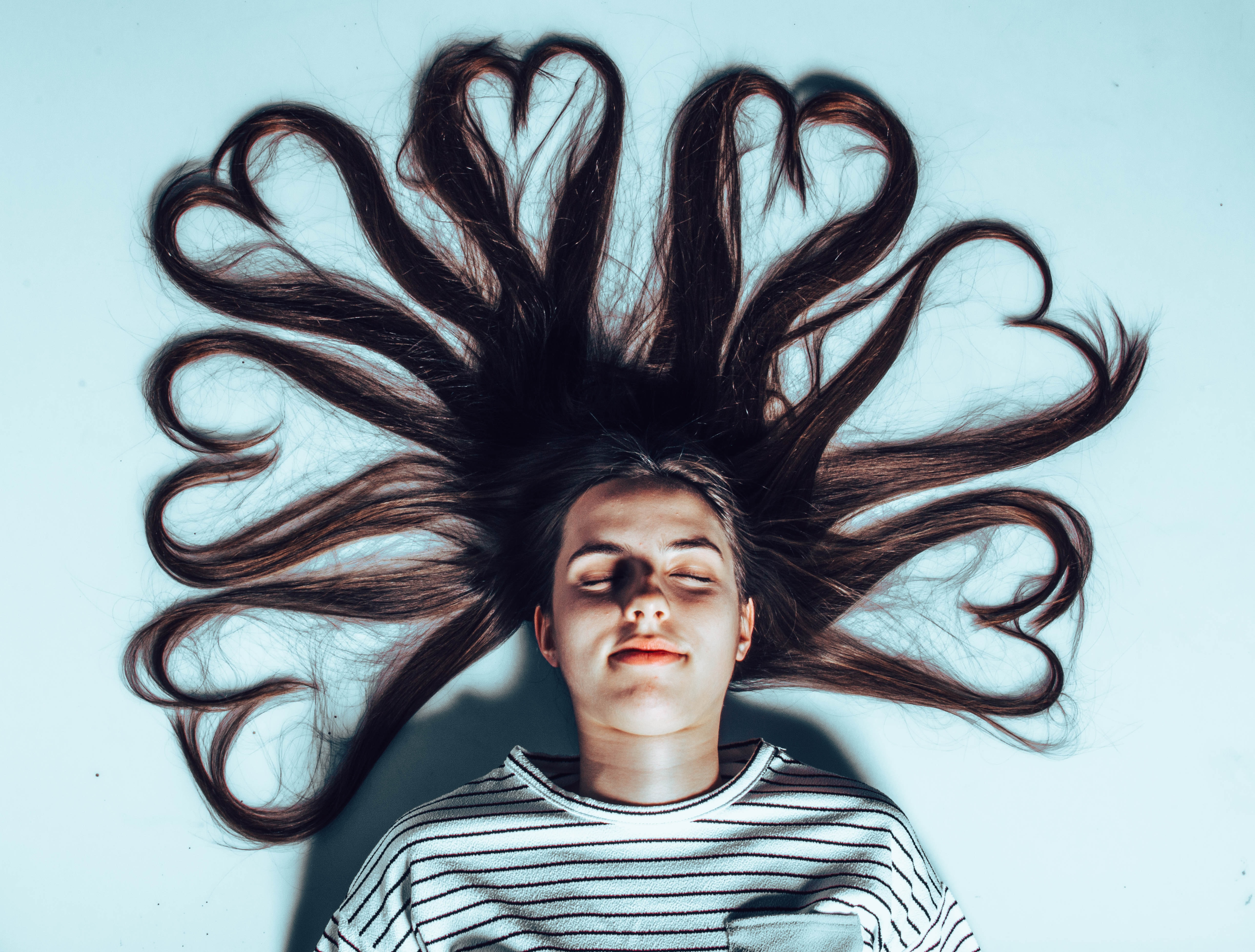 woman laying on white surface with heart forming hair