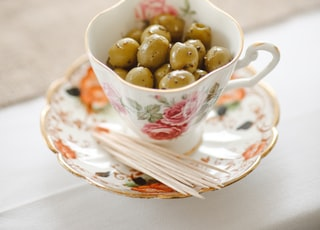 saucer plate with cup, beans and stick