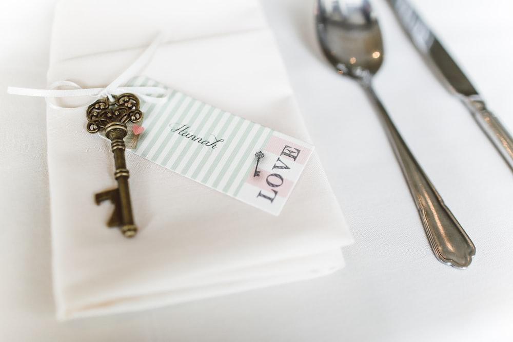 silver skeleton key on white textile