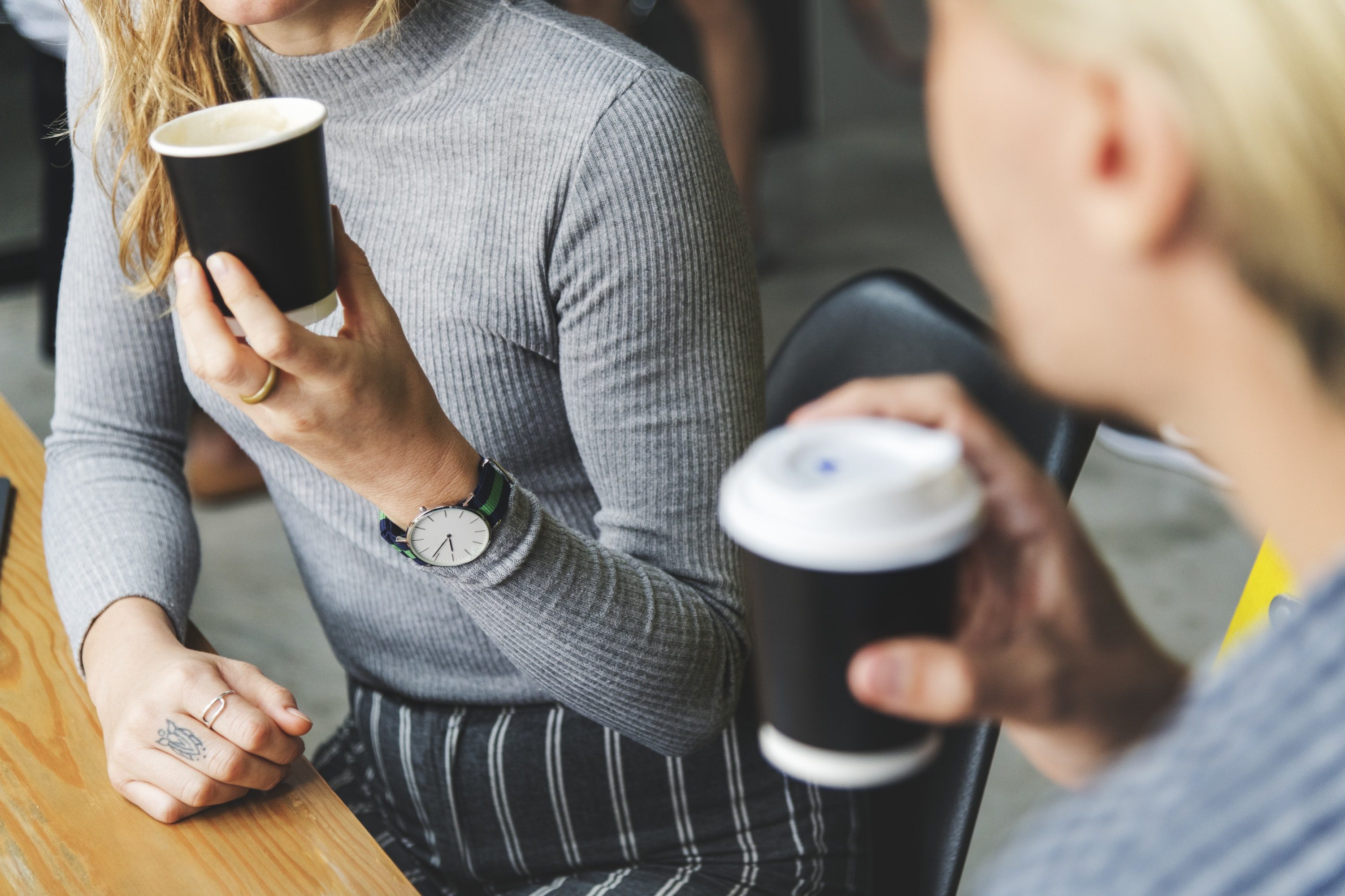 two women talking while holding coffee cups