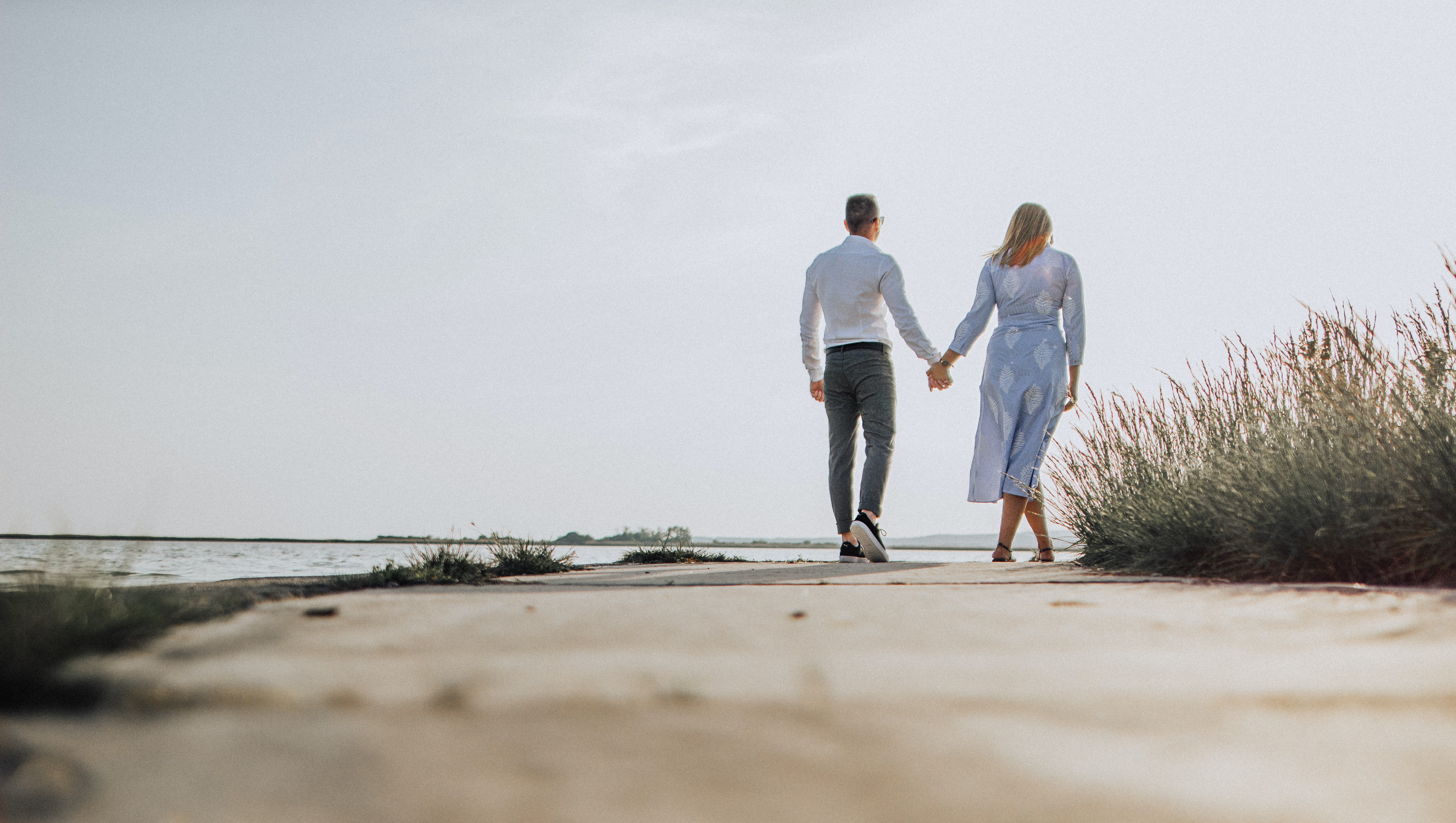 couple holding hands with standing on shore