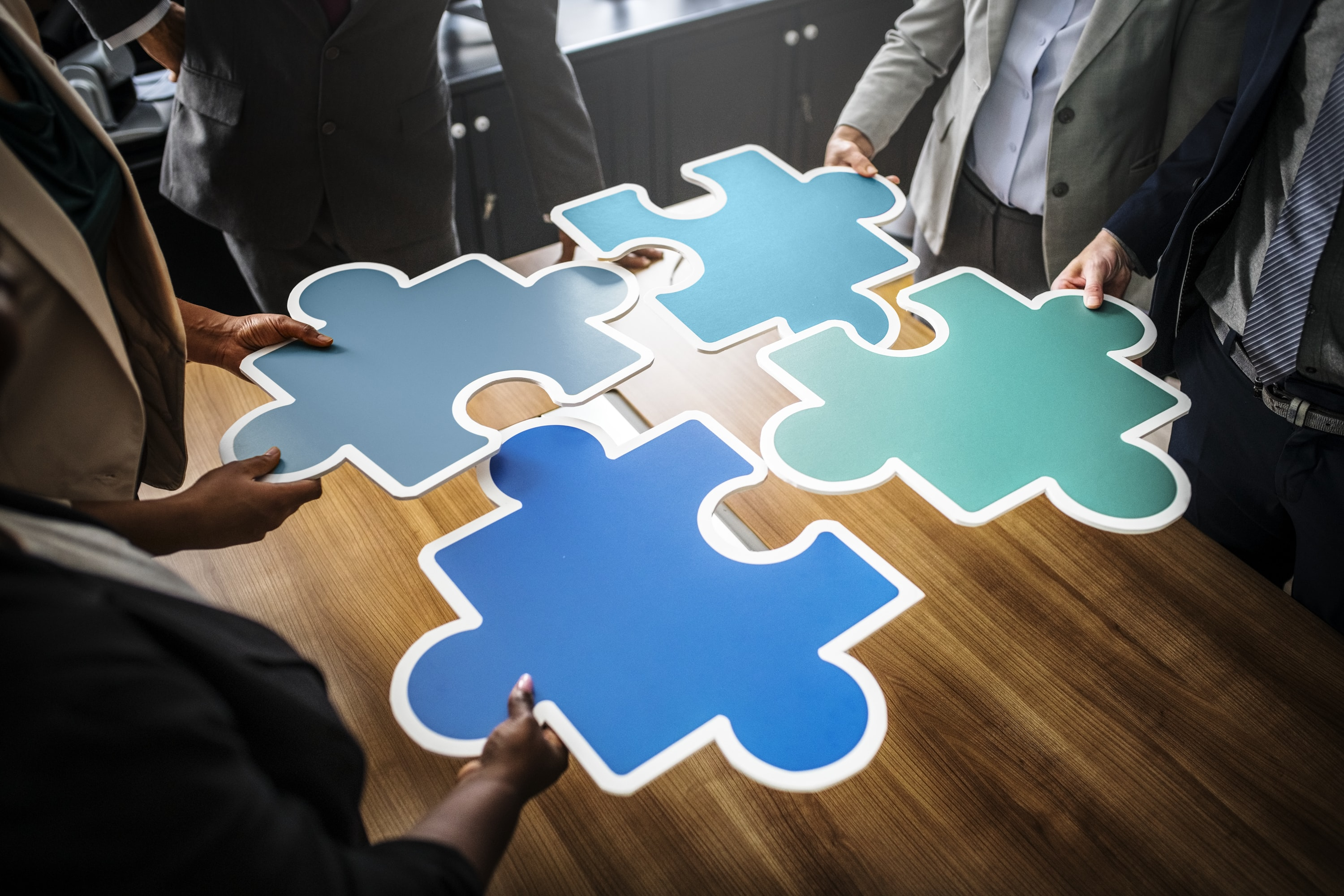 four person holding assorted-color jigsaw puzzles inside room