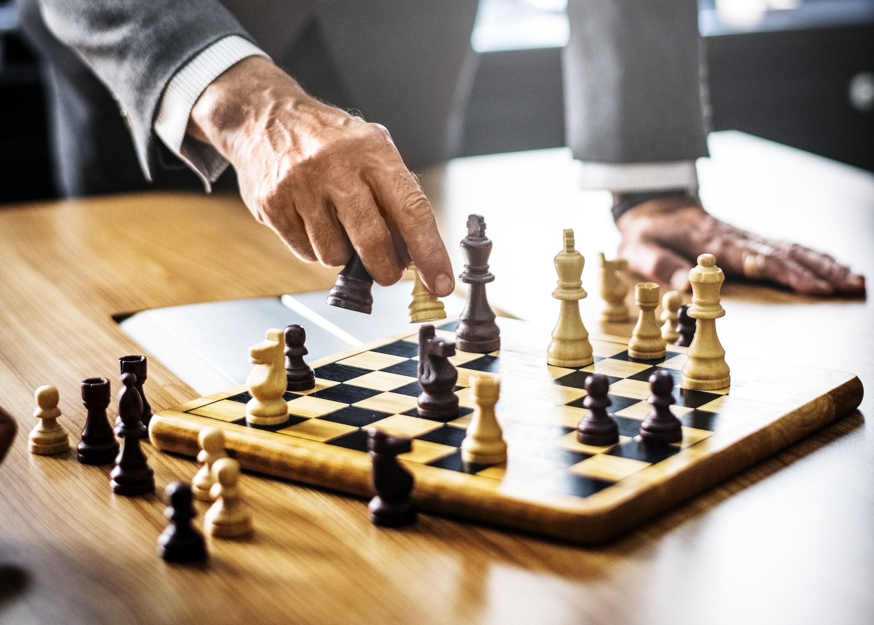 person holding chess piece on top of table