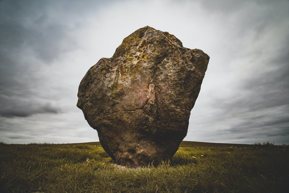 brown rock formation surrounded by green grass