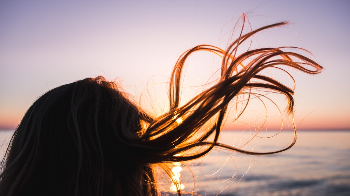A woman with long brown hair blowing in teh wind watching the sun set over water.