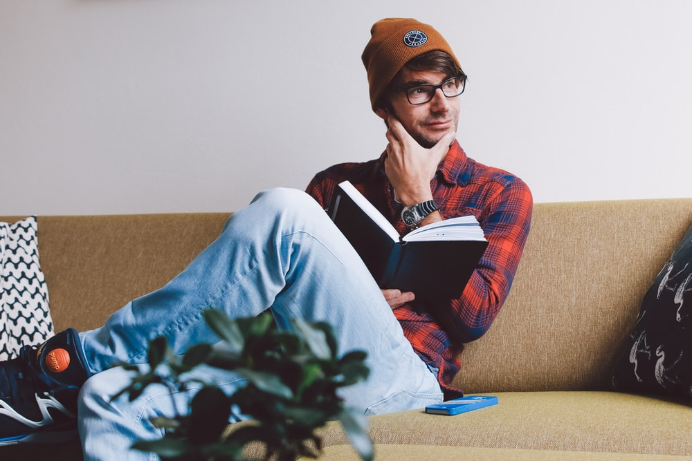 man sitting on sofa while holding book