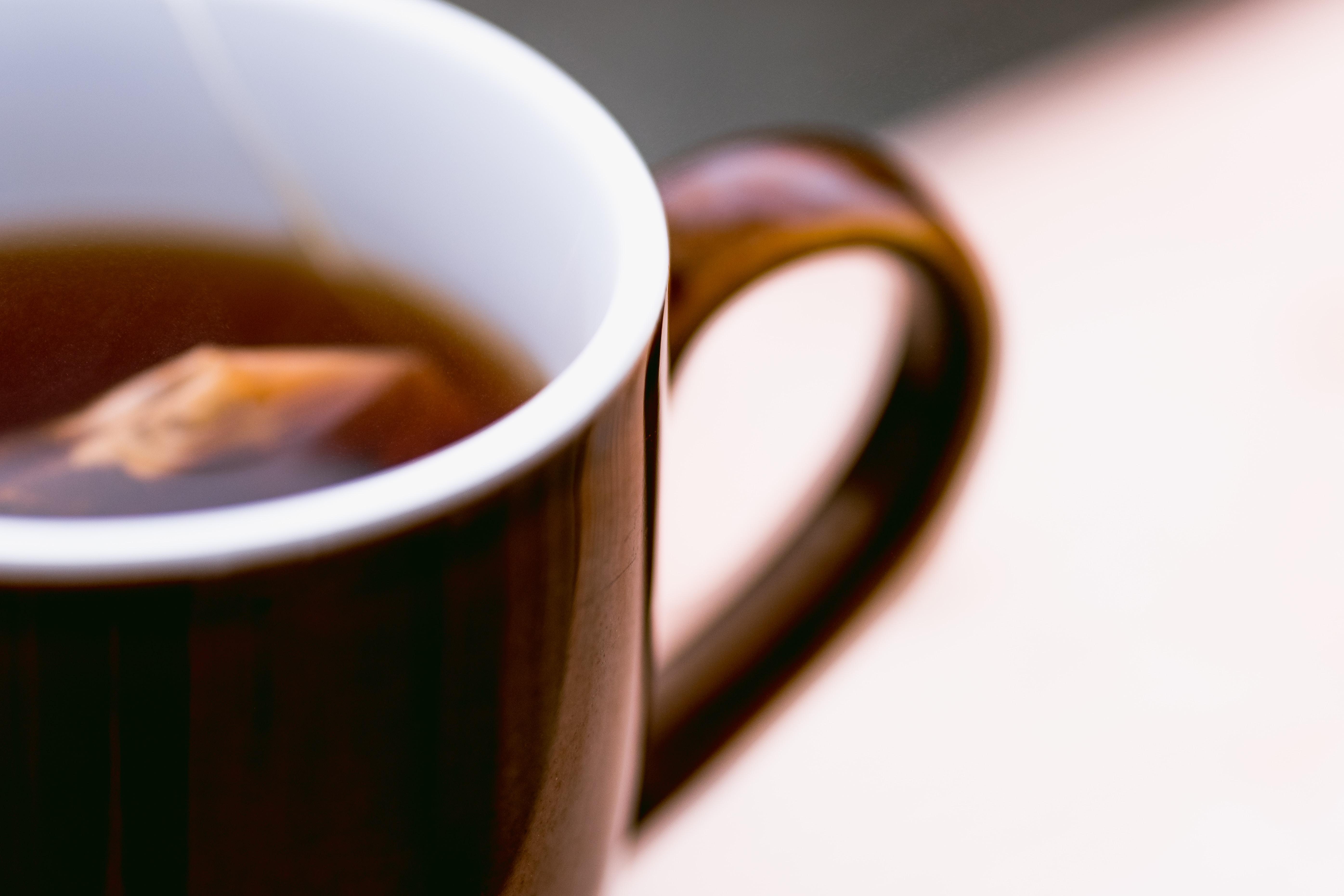 brown ceramic mug with brown liquid inside
