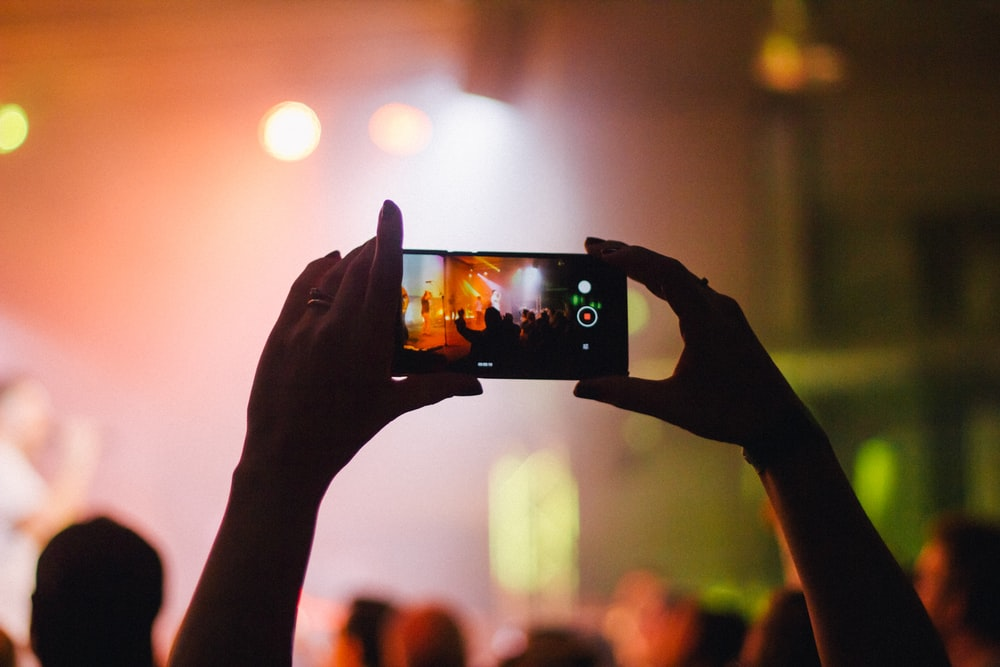 person holding smartphone while taking videos at live concert