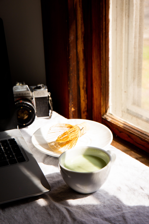 white ceramic tea cup beside white ceramic plate