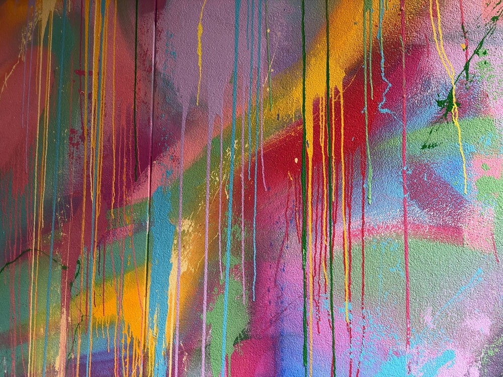 teal, pink, and yellow abstract painting