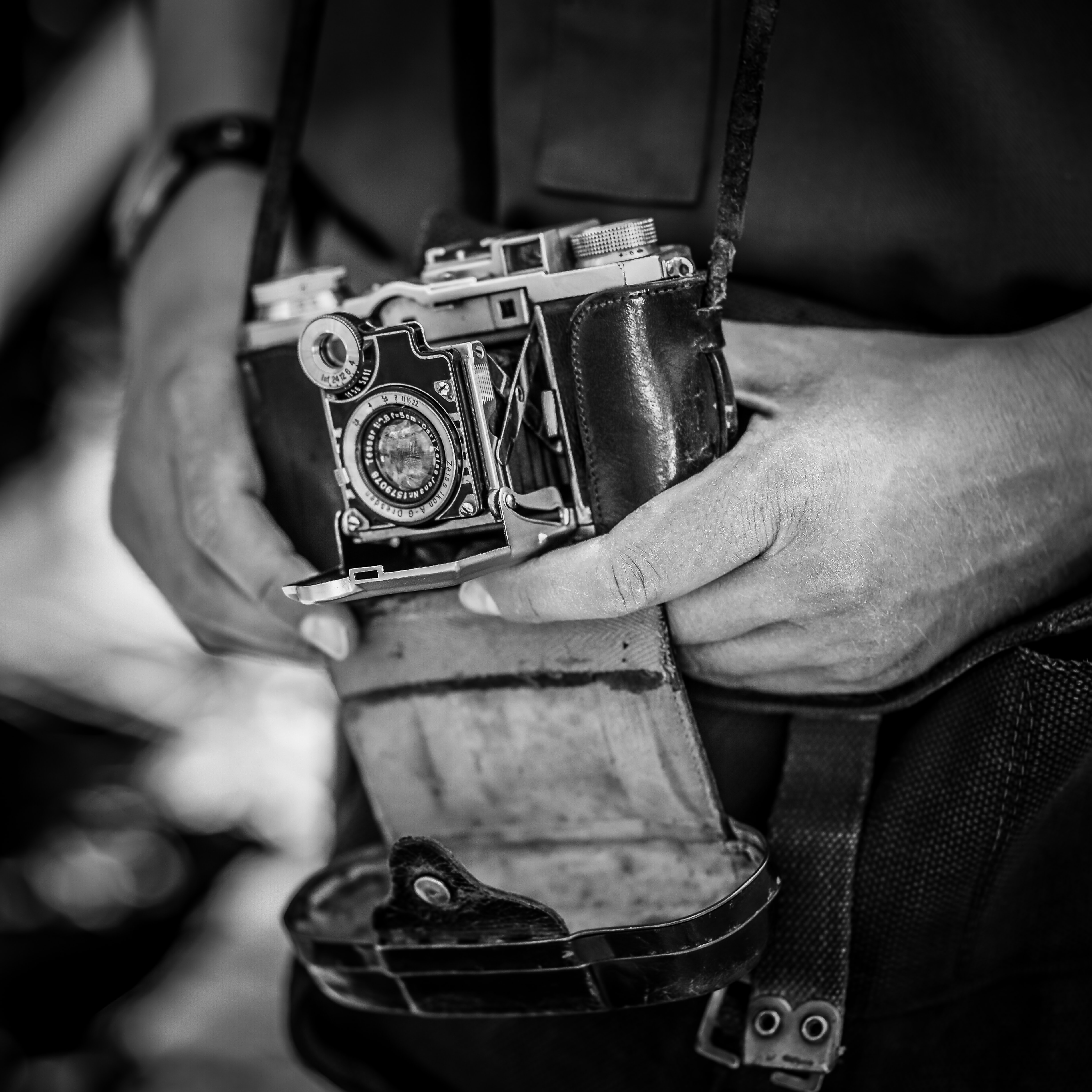grayscale of person holding SLR camera