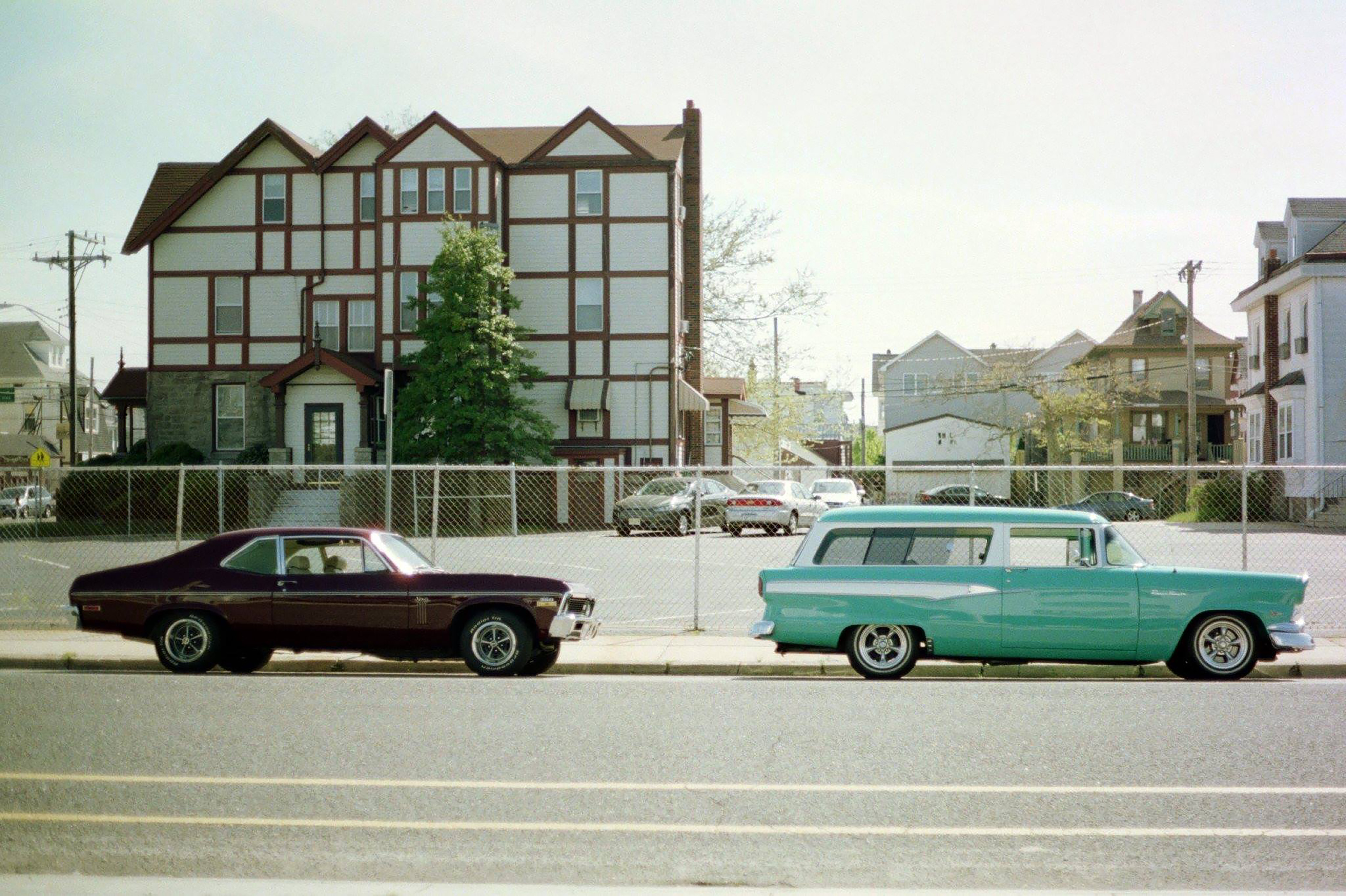 two brown and green coupes beside houses