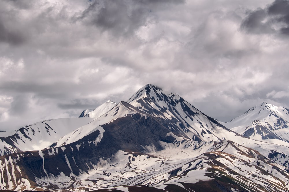 mountain filled with snow under cloudy sky