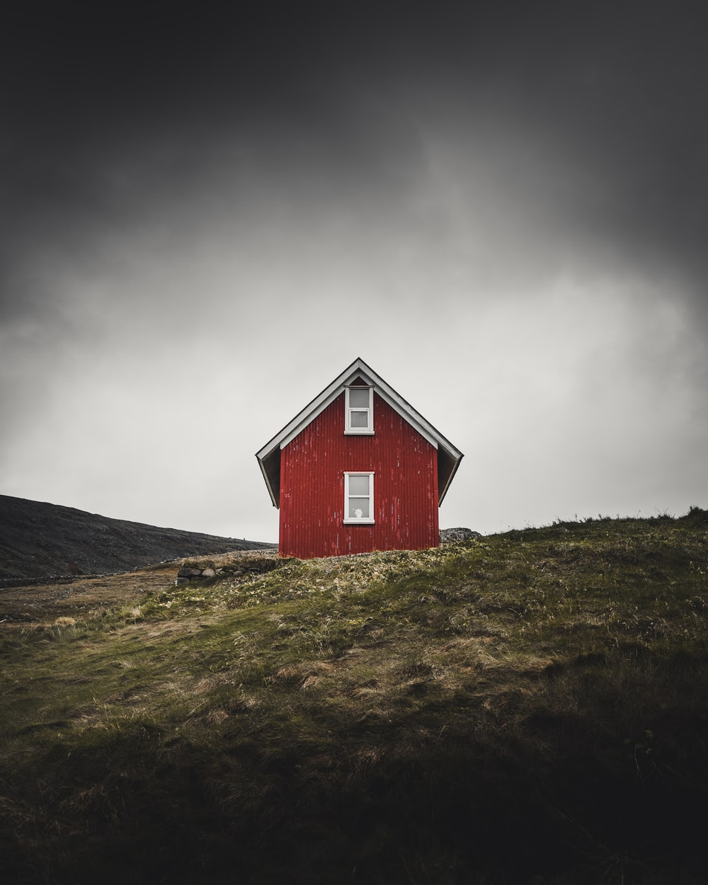 photo of red barn house on top of hill