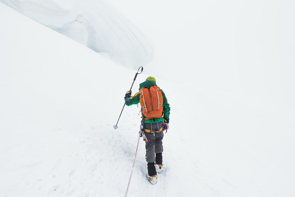 person walking on snow covered mountain