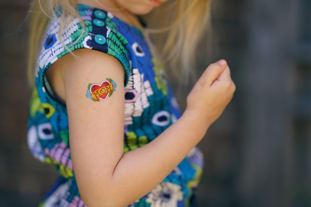 selective focus photo of girl with heart tattoo