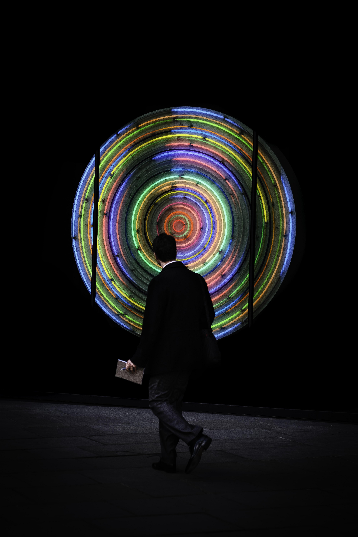 man walking while looking at neon signage